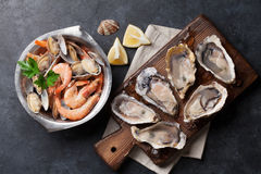 Fresh seafood. Scallops, oysters and shrimps. Fresh seafood on stone table. Scallops, oysters and shrimps. Top view stock images