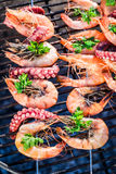 Fresh seafood skewers with lemon and parsley on grill Stock Photos