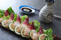 Fresh seafood. Slices or pieces of fresh seafood between lime wedges with sake pitcher and soy sauce Royalty Free Stock Photos