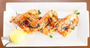Fresh seafood starter of grilled prawns. Fresh seafood starter of grilled whole prawns or shrimps served with chopped fresh herbs and tangy lemon garnish to royalty free stock photo