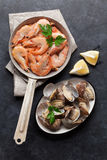 Fresh seafood on stone table. Scallops and shrimps Royalty Free Stock Photos