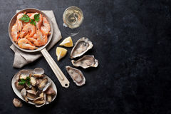 Fresh seafood and white wine. Scallops, oysters and shrimps Royalty Free Stock Photos