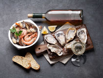 Fresh seafood and white wine on stone table Stock Photos