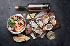 Fresh seafood and white wine. On stone table. Oysters, prawns and shells. Top view Royalty Free Stock Image