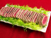 Fresh Seared tuna fish slices on tray. Fresh Seared tuna fish slices on white porcelain tray with green leaves for decoration. Red tablecloth as background Stock Photo