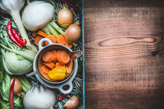 Fresh seasonal organic local vegetables box for healthy clean eating and cooking on rustic wooden background, top view, place for. Text. Vegan or vegetarian Stock Photos