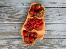 Fresh,seasonal raspberries and strawberries in sculpted wood platter Stock Images