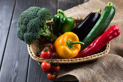 Fresh seasonal vegetables in basket on rustic wooden table Stock Photos