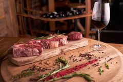 A fresh, seasoned Ribeye steak on a cutting board with pepper, rosemary. Near a glass of red wine royalty free stock photography