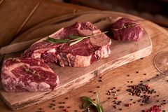 Fresh, seasoned Ribeye steak on a cutting board with pepper, rosemary, sun-dried tomatoes. Next to a glass of red wine. royalty free stock photos