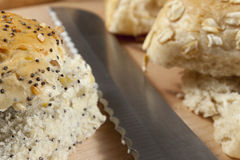 Fresh seeded bread rolls laying next to a knife Stock Images