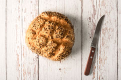 Fresh seedy bread with knife on a white wooden Stock Images