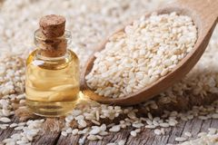Fresh sesame oil in a glass bottle and seeds in a wooden spoon Royalty Free Stock Photography