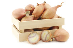 Fresh shallots and a cut one in a wooden box Royalty Free Stock Image