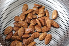 Fresh shelled almonds in a colander. Fresh shelled almonds in a stainless steel colander or sieve ready to be used as an ingredient in baking or cooking, close Stock Images
