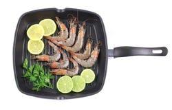 Fresh shrimps on black pan. Isolated on a white background Stock Photos