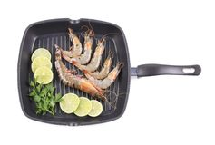 Fresh shrimps on frying pan with lemon slices. Royalty Free Stock Photo