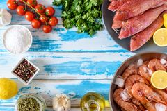 Fresh shrimps and red mullet fish on blue wooden background. With herbs and spices. Flat lay Royalty Free Stock Images