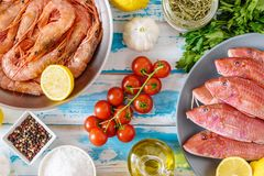Fresh shrimps and red mullet fish on blue wooden background. With herbs and spices. Flat lay Stock Photos