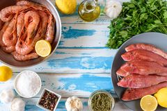 Fresh shrimps and red mullet fish on blue wooden background. With herbs and spices. Flat lay Royalty Free Stock Photos