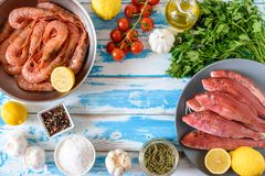 Fresh shrimps and red mullet fish on blue wooden background. With herbs and spices. Flat lay Stock Photography