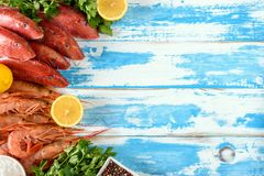 Fresh shrimps and red mullet fish on blue wooden background. With herbs and spices. Flat lay Royalty Free Stock Image