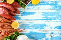Fresh shrimps and red mullet fish on blue wooden background. With herbs and spices. Flat lay Stock Photo