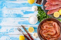 Fresh shrimps and red mullet fish on blue wooden background. With herbs and spices. Flat lay Stock Image