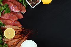 Fresh shrimps and red mullet fish on dark stone background. With herbs and spices. Flat lay Stock Photo