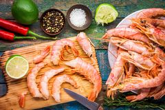 Fresh shrimps on wooden board with salt, chili pepper, lime Royalty Free Stock Photo
