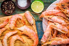 Fresh shrimps on wooden board with salt, pepper, lime closeup Royalty Free Stock Photos