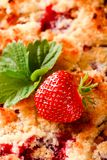 Fresh single strawberry on fruit pie with berries. Vertical photo of red juicy strawberry and strawberry green leaf placed on fruit pie. Baked fruit cake made Stock Photos