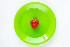 Fresh single strawberry in green plate Stock Images