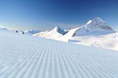 Fresh ski track at Hintertux. Groomed ski track at Hintertux glacier and mountain summits at background Stock Images