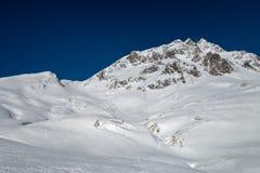 Fresh ski tracks leading down from alpine mountain ridge over  Royalty Free Stock Images
