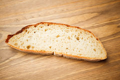 Fresh slice of bread. On wooden plank Royalty Free Stock Image