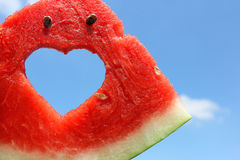 Fresh slice of watermelon with heart inside. On blue sky as congratulations on Valentine's Day royalty free stock image