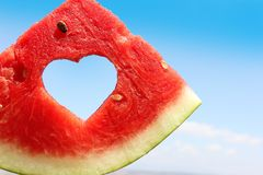 Fresh slice of watermelon with heart inside. On blue sky background stock images