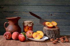 Fresh sliced ��peaches and a ceramic jug Stock Images