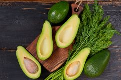 Fresh sliced avocados and dill on the wooden board. Raw ingredients for veggie healthy or diet dish on the black background. Top view royalty free stock photos