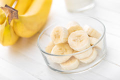 Fresh sliced bananas on white wooden background closeup. Healthy eating Royalty Free Stock Images