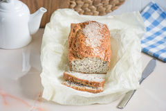 Fresh sliced bread with bran with sesame, bran and flax seeds, d. Freshly baked bread with bran from oat flour with sesame seeds and flax seeds, on paper for Stock Photos