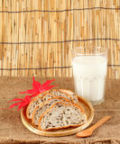 Fresh sliced bread in a wicker basket with mik. Stock Images