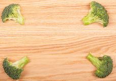 Fresh sliced broccoli pieces on the background  light wood. Fresh sliced broccoli pieces on the background of light wood Stock Images