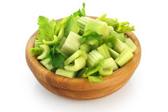 Fresh sliced celery in a wooden bowl isolated on white backgroun Royalty Free Stock Image