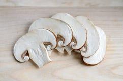 Fresh champignon mushrooms. Fresh sliced champignon mushrooms on wooden chopping board Stock Photography