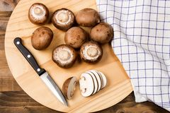 Fresh and sliced chestnut mushroom on a wooden board royalty free stock photos