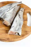 Fresh sliced hake fish filets on the cuting wooden board.  Royalty Free Stock Photos