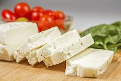 Fresh sliced halloumi cheese. From Cyprus on a wooden board surface Stock Images