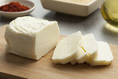 Fresh sliced halloumi. Piece of fresh sliced halloumi on a cutting board Stock Images